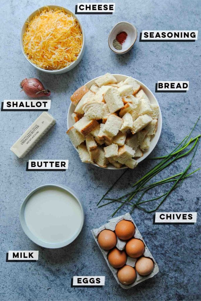 cheddar cheese, salt, pepper, paprika, shallot, butter, cubed bread, chives, milk, and eggs