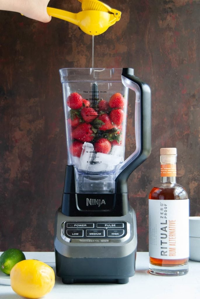 squeezing citrus juice into a blender with strawberries and ice