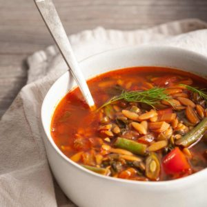cropped soup bowl with vegan orzo soup and a spoon