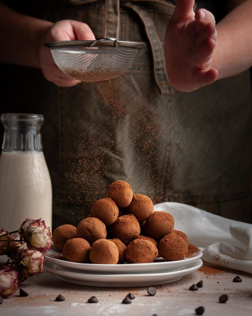 action shot of dusting chocolate truffles with cocoa powder