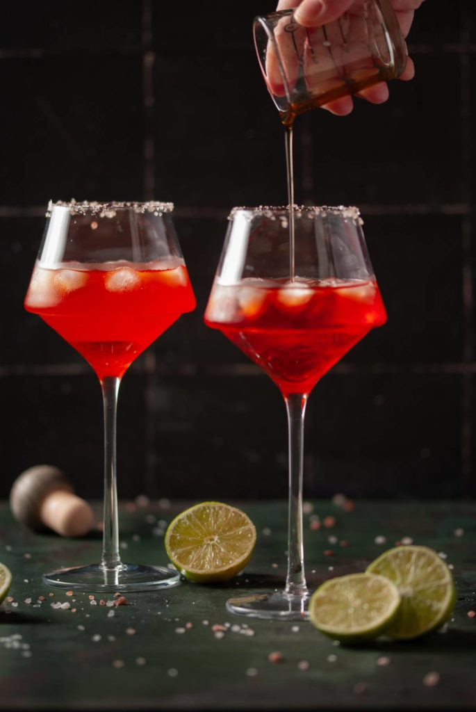 Pouring Agave Nectar Into Bright Red Cocktail