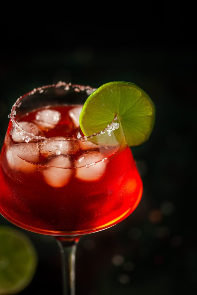 Close Up of Salt Rimmed Glass With Ice and Red Cocktail Garnished With Lime