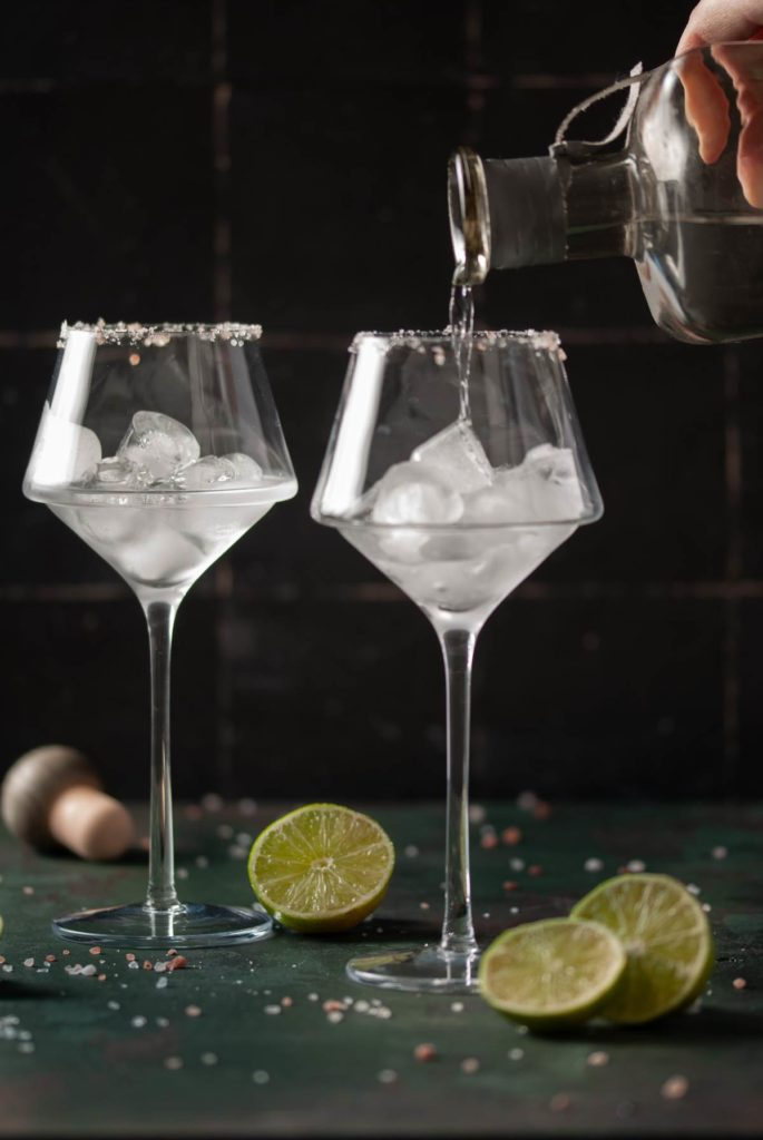 Pouring Tequila Into Wine Glasses With Ice
