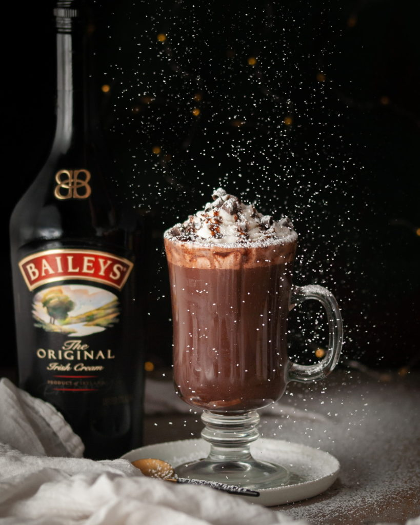 Bailey's Hot Chocolate with Confectioner's Sugar Being Dusted on Top