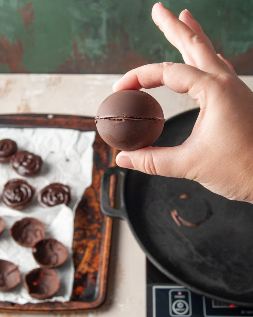 Sealing two chocolate half spheres to form a hot chocolate bomb