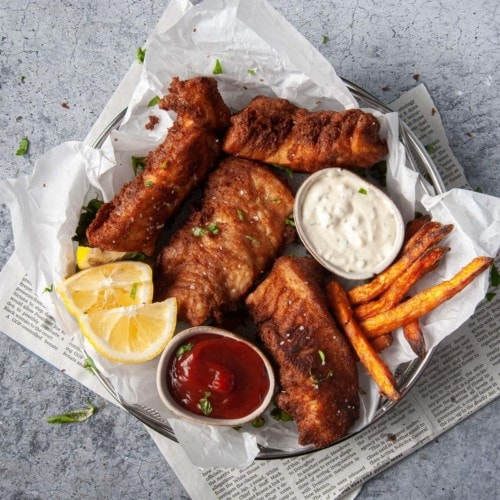 overhead photo of beer battered halibut with fires, dipping sauces, and lemon wedges