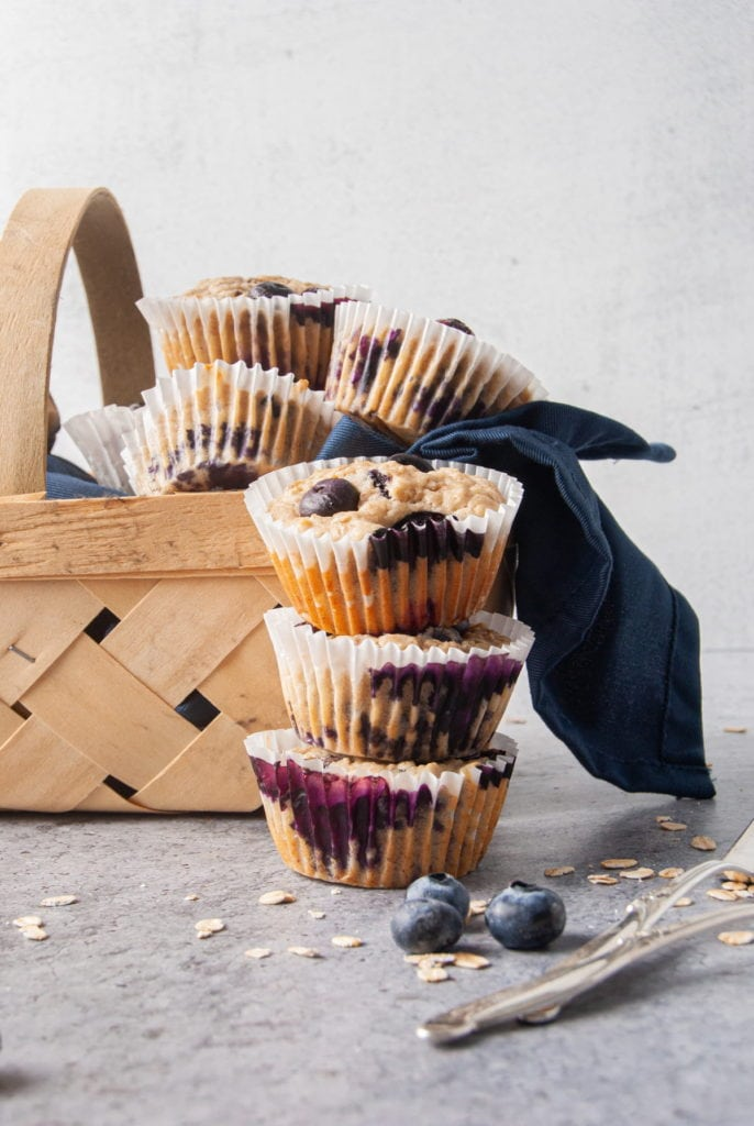 Stack of Muffins with Blueberries in front of a basket of muffins
