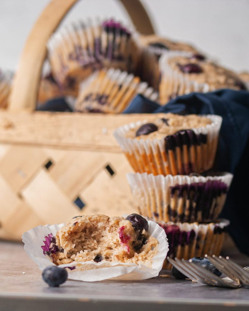 blueberry banana muffin with a bite taken out of it surrounded by more muffins