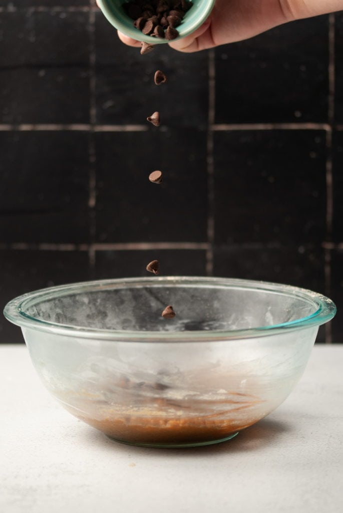 dropping chocolate chips into a bowl