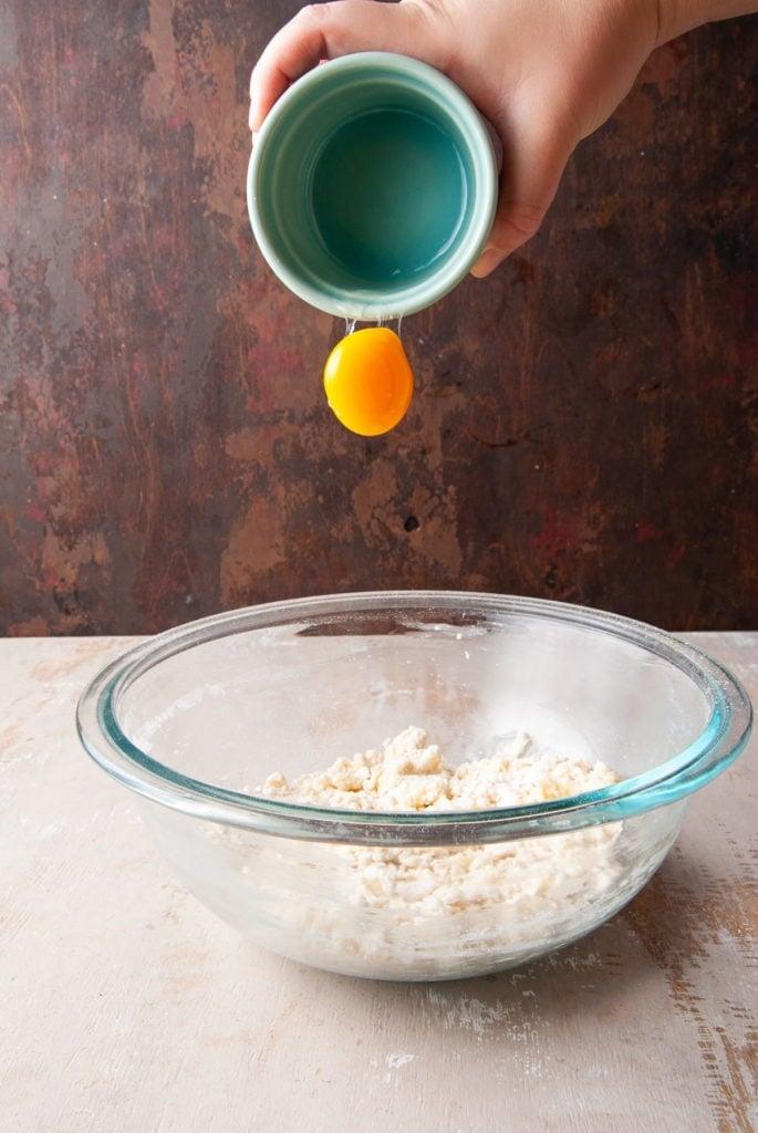 adding egg yolk to shortbread cookie dough