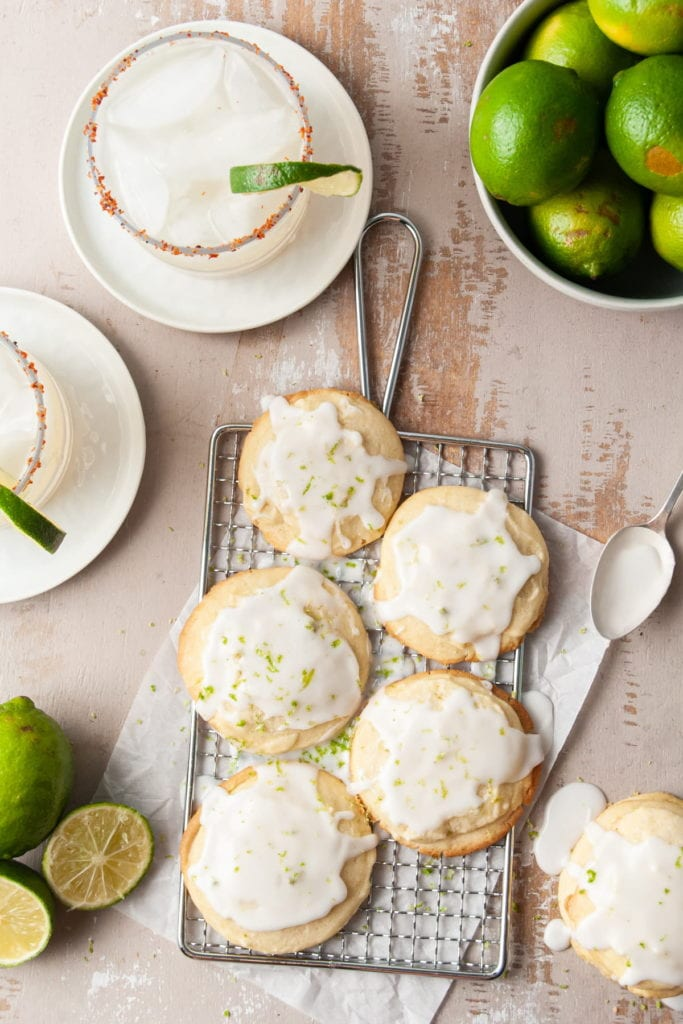 portrait of glazed shortbread cookies surrounded by margaritas and limes