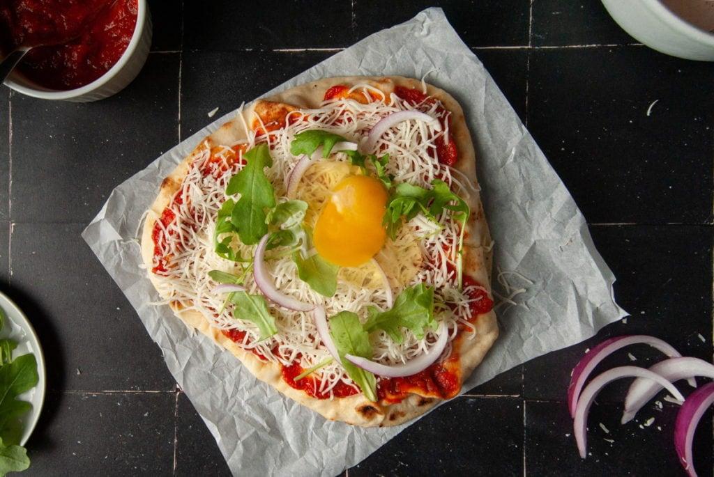 Cracking an Egg onto Naan Pizza