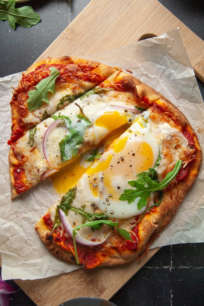 Slicing into Naan Breakfast Pizza with Yolk Oozing