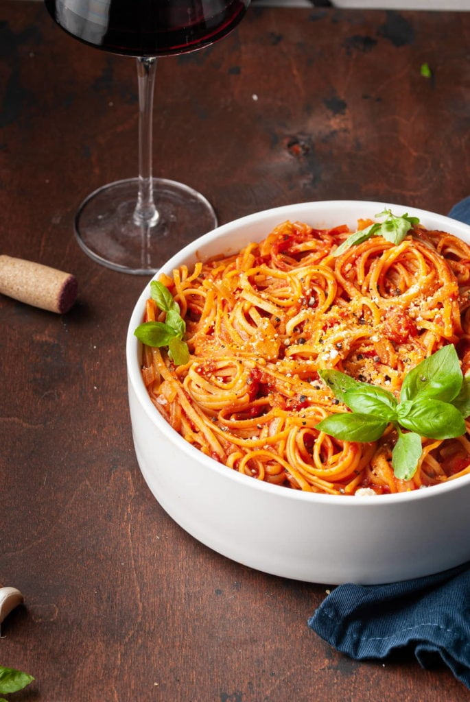 cropped serving bowl with pasta with tomato sauce and glass of wine