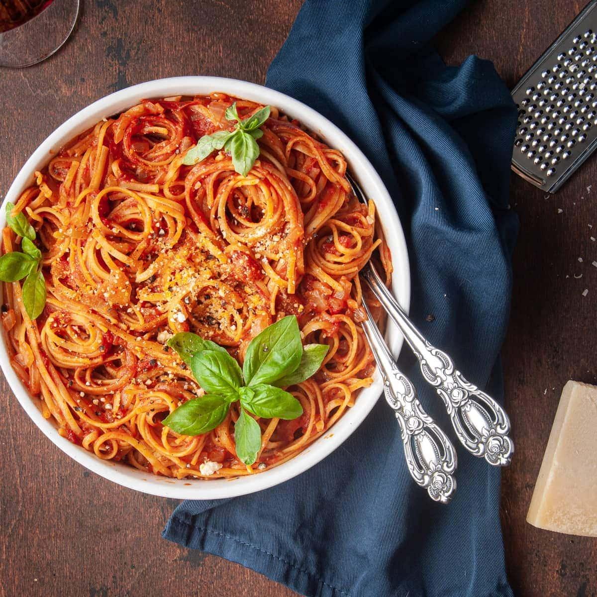 one-pot vegan pasta with tomato sauce next to parmesan cheese