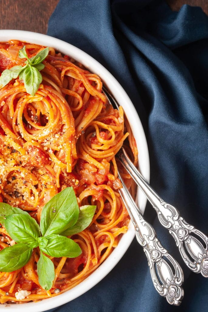 close up of pasta with tomato sauce and basil