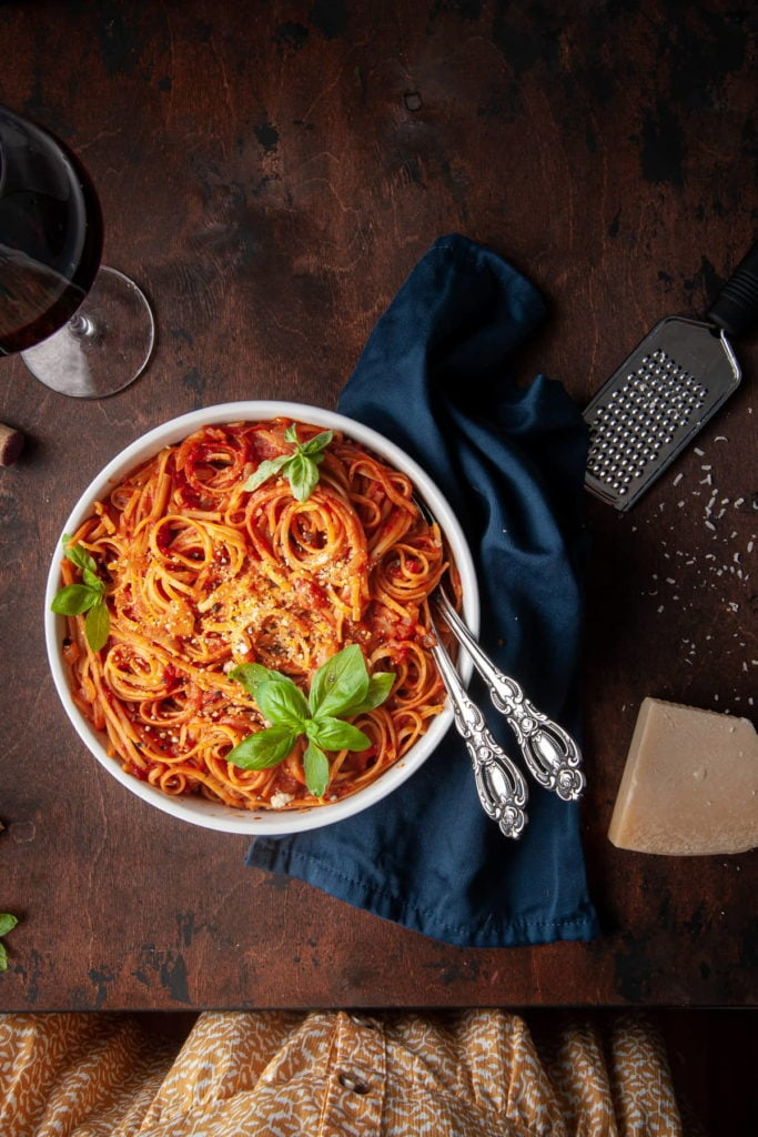 overhead shot of pasta with tomato sauce and woman's dress whowing