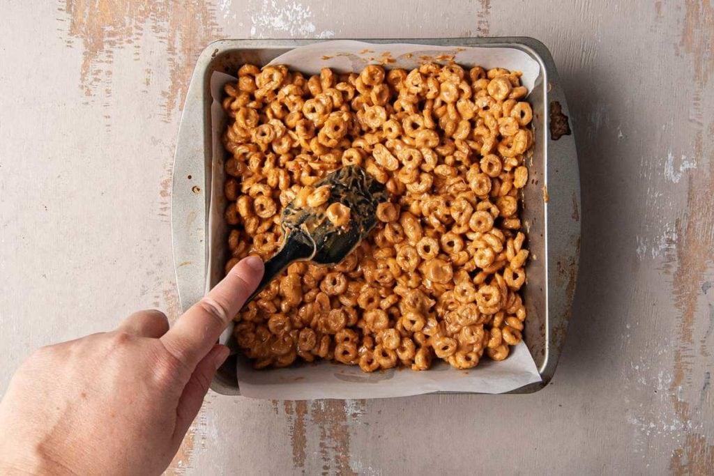 pushing cheerio bar mixture into cake pan to set
