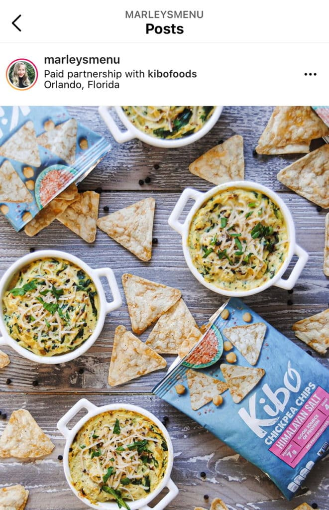 Screenshot of a sponsored post on Instagram, picture of chips and vegan cheesy spinach dip