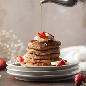 stack of whole wheat strawberry banana pancakes with syrup being poured on top