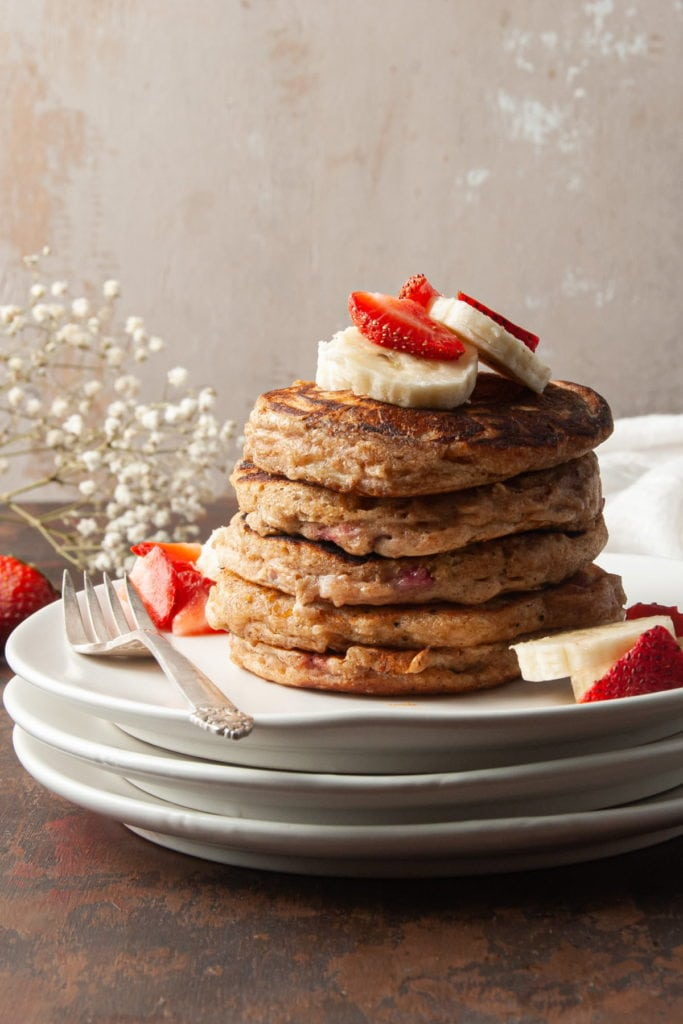 tall stack of whole wheat pancakes topped with bananas and strawberries
