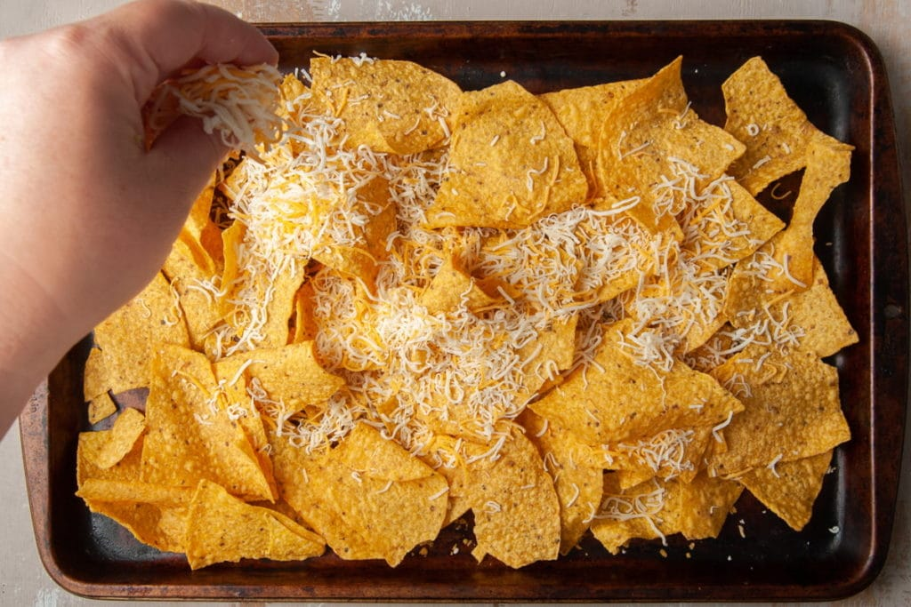Adding shredded cheese to chips on sheet pan