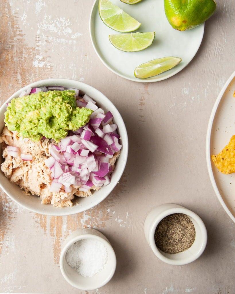 adding avocado, red onion, and lime juice to tuna