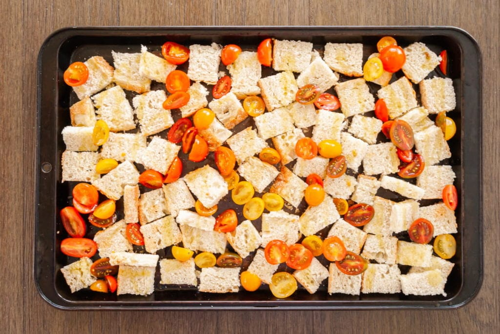 adding panzanella ingredients to sheet pan to add to oven