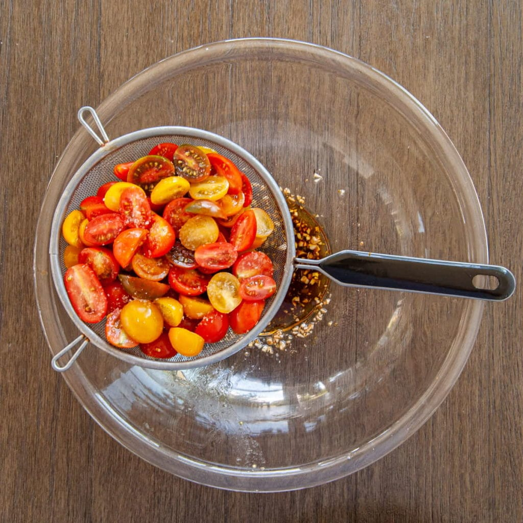 straining liquid from tomatoes with salt