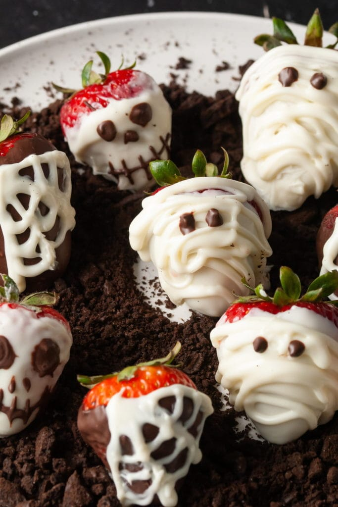 chocolate covered strawberries decorated with spiderwebs mummies and skeletons