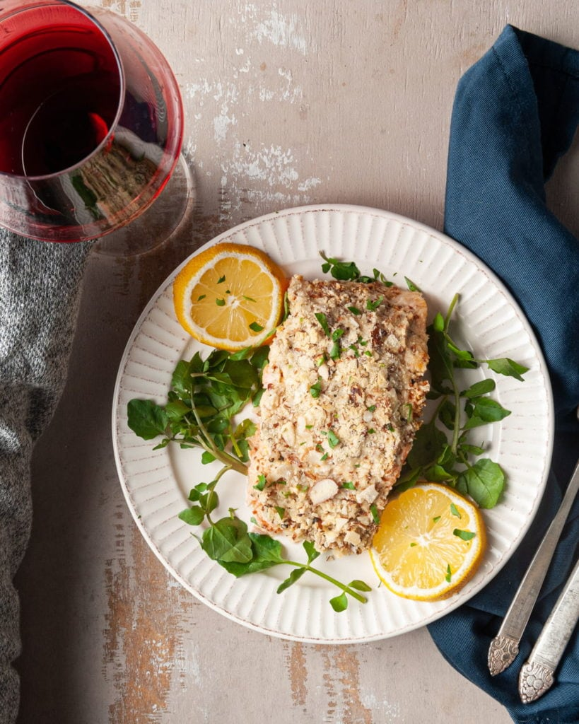 hand grabbing wine next to plate of salmon