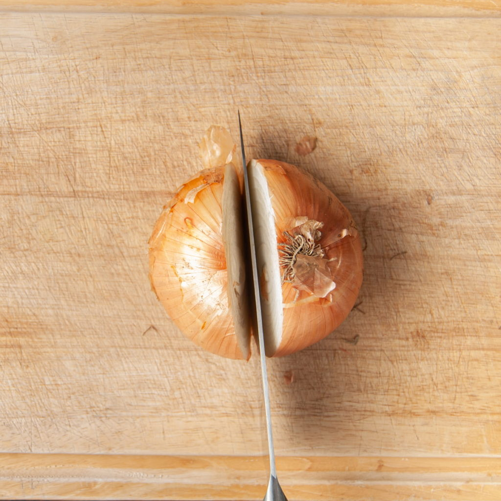 slicing yellow onion in half