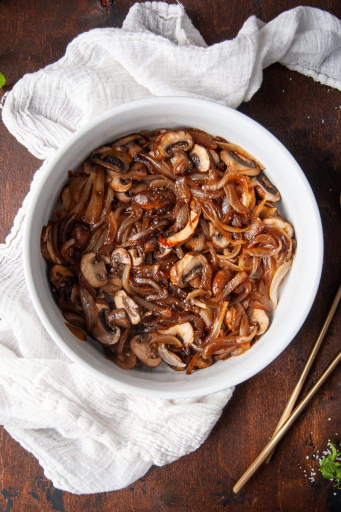 caramelized onions and mushrooms in a serving bowl with gold serving utensils