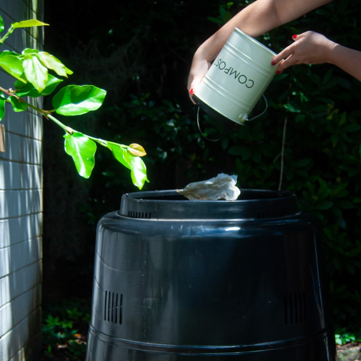 pouring kitchen compost pail into outside compost bin to represent advantages of composting