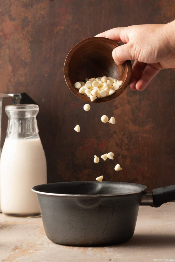 pouring white chocolate chips into a small pot