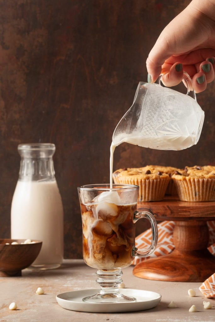 pouring white chocolate milk into iced latte
