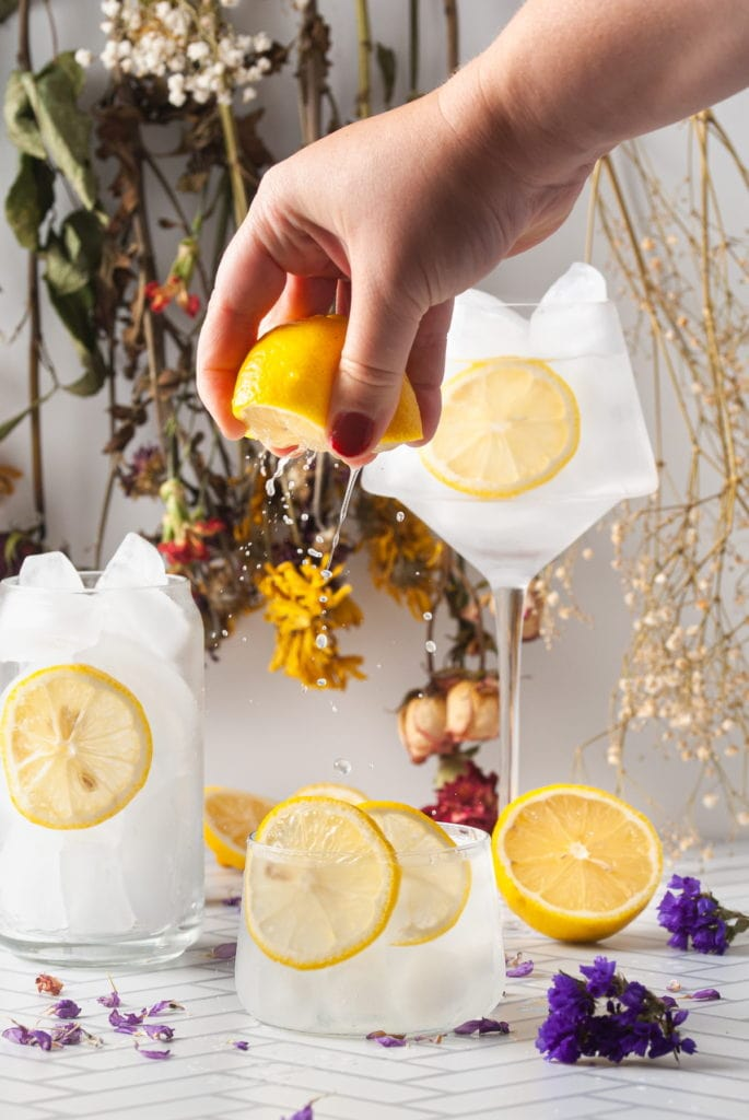 squeezing lemon over a vodka sour to give it extra citrus