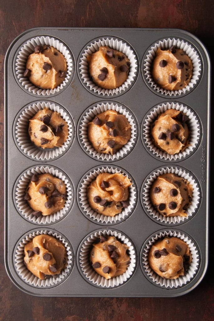 muffin tin filled with peanut butter chocolate chip muffin batter