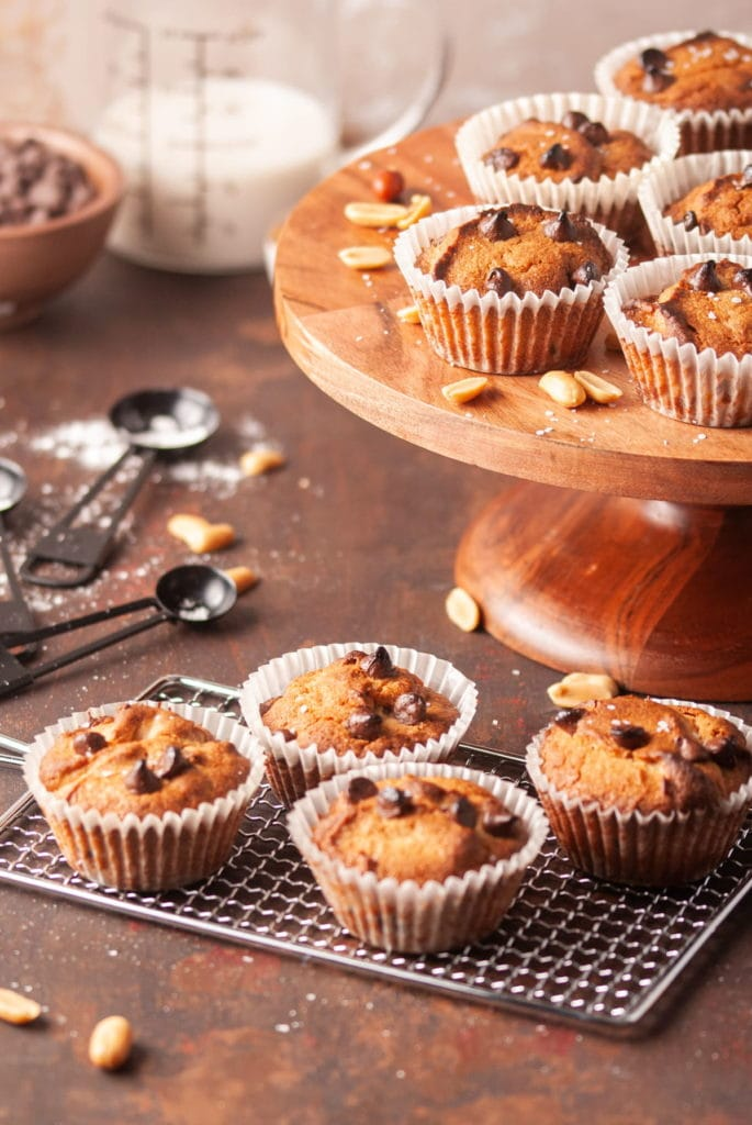 peanut butter chocolate chip muffins on a cooling rack with more muffins on a cake stand in the background