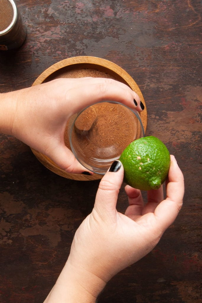 wetting the rim of a lowball glass with a lime