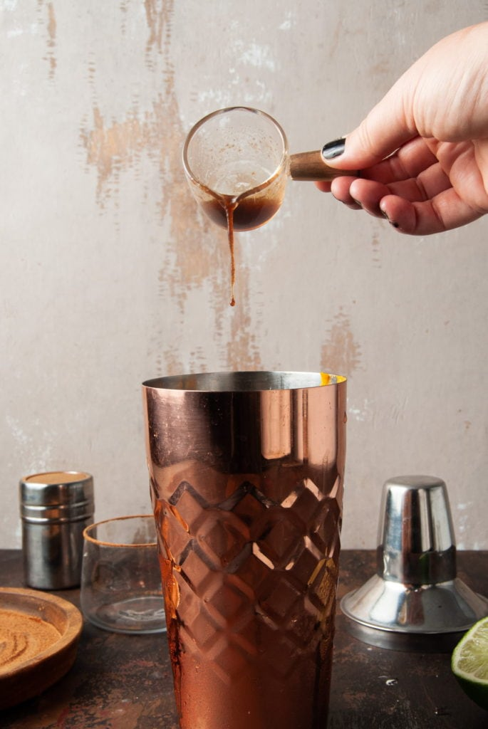 pouring pumpkin spice simple syrup into a copper cocktail shaker