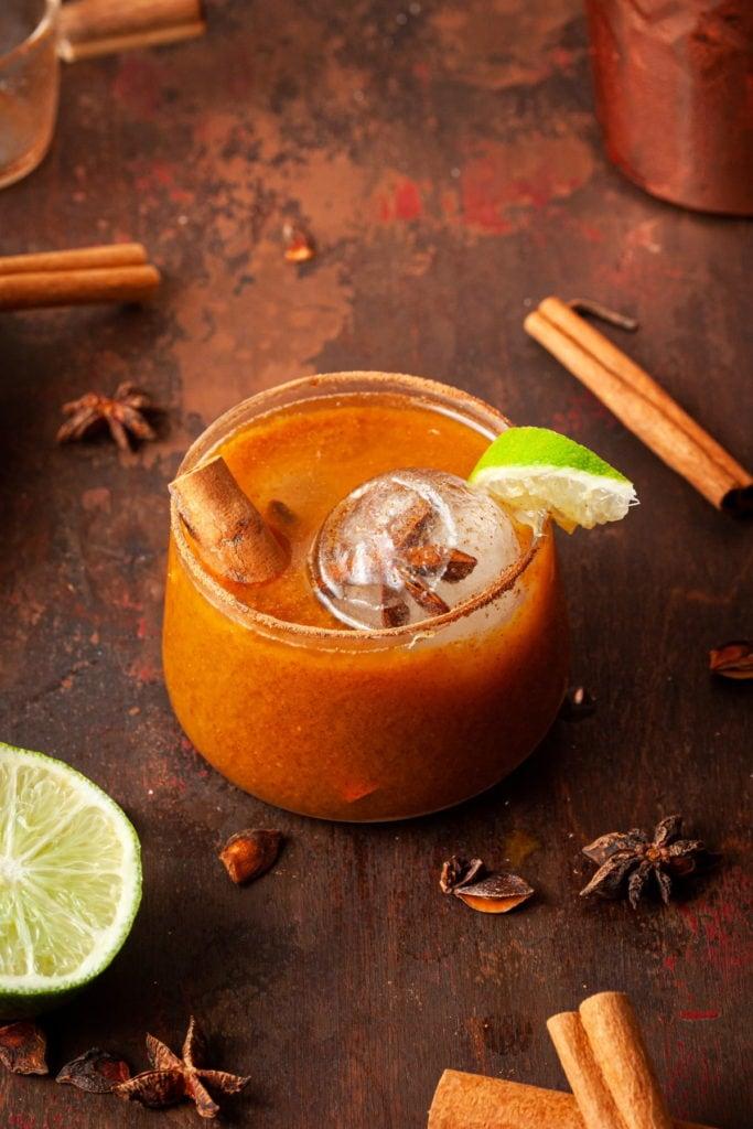 orange margarita garnished with lime and a cinnamon stick