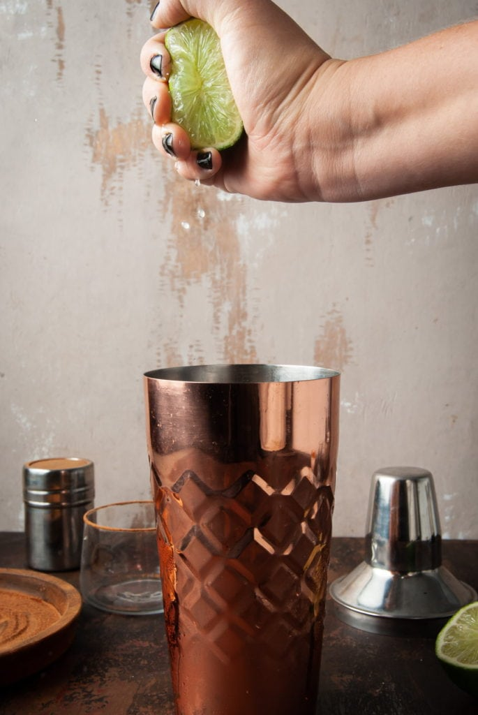 squeezing a lime into a copper cocktail shaker