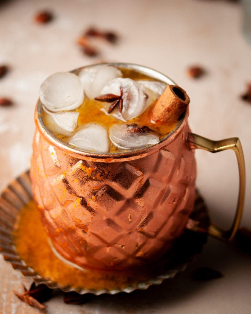 45 degree angle shot of an ice cold mule with a cinnamon stick