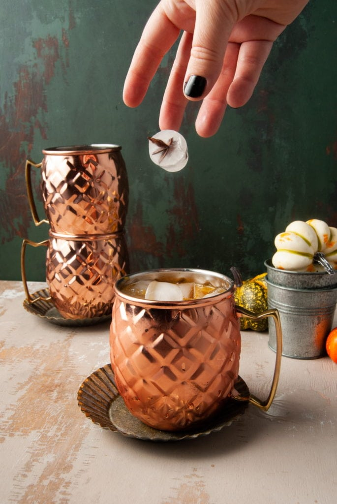 adding ice with star anise inside to copper mug