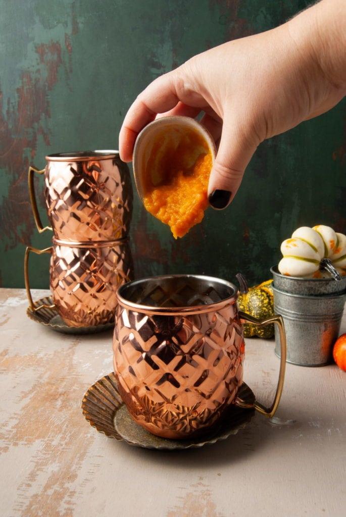 adding pumpkin puree to a copper mug