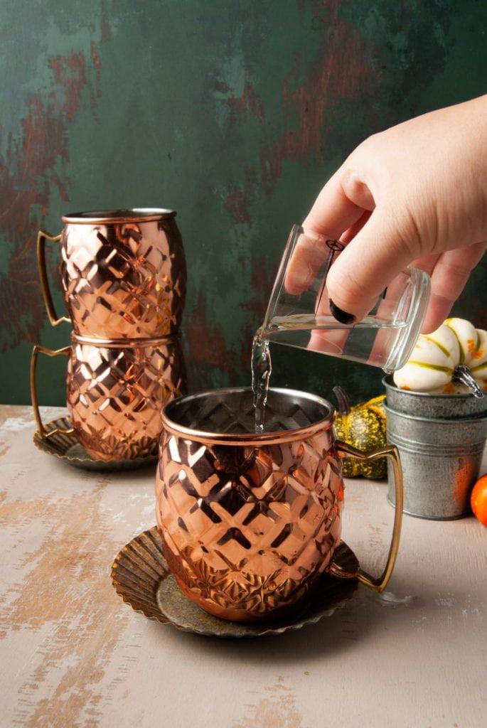 pouring vodka into a copper mug