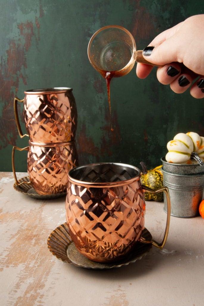 adding pumpkin spice simple syrup to copper mug