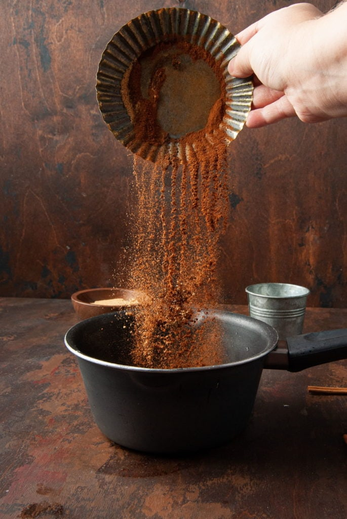 adding pumpkin pie spice to a pot with water