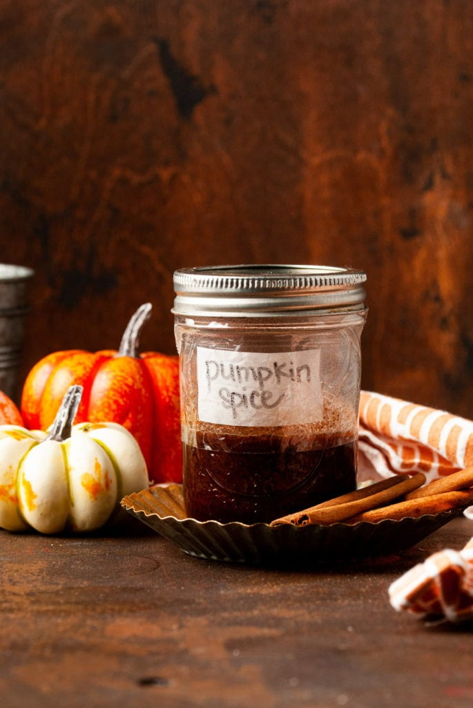 pumpkin spice simple syrup in a sealed jar surrounded by little pumpkins